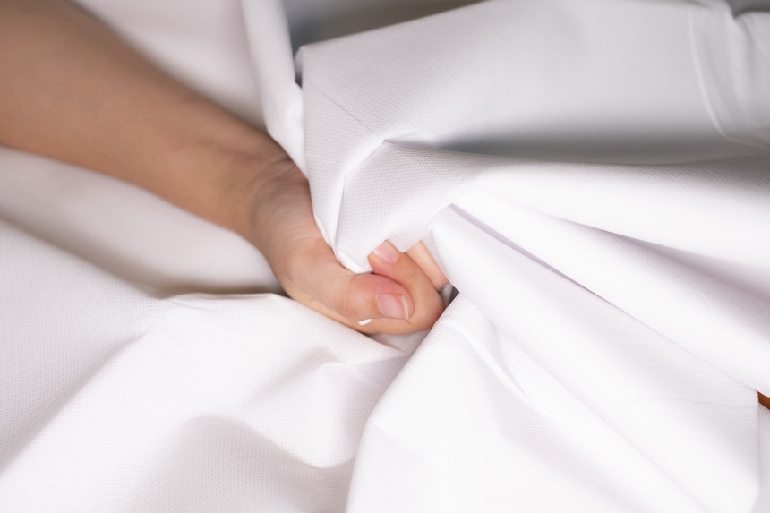Woman hand squeezing bed sheets color white